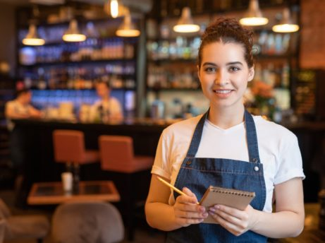 Young smiling waitress in workwear standing in luxurious restaurant